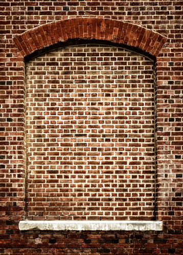 A bricked up window with an arched head