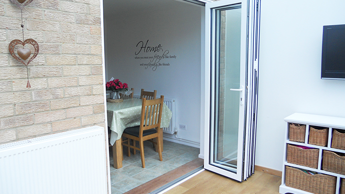 Bi-fold doors from house to a conservatory in white